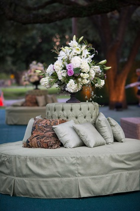 Round tufted bench in light green with flower arrangement with hydrangea, lily, rose flowers