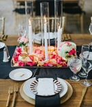 three tapered white candles in hurricanes on platter of peach and hot pink flower petals