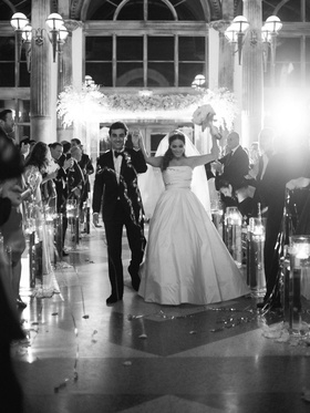 black and white photo of bride and groom walking up aisle as husband and wife confetti explosion
