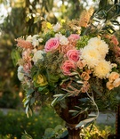 a cluster of pink white and green flowers and leaves in gold vase outside couples ceremony space