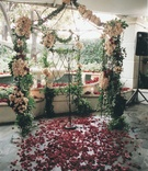 Flower wedding arch in front of fountain with red rose aisle