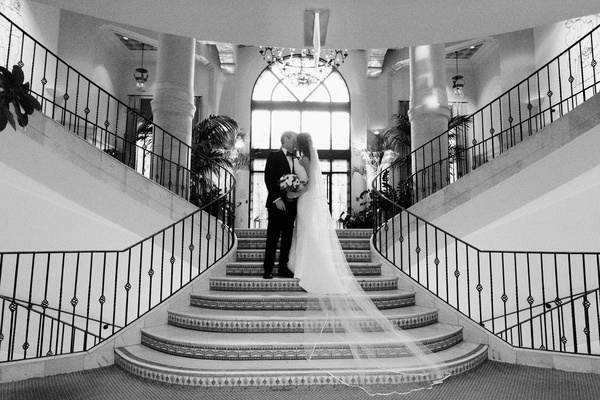 black and white photo of bride and groom kissing on the stairs of casa del mar