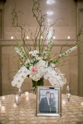 couple photo eclectic floral arrangement orchids hydrangea branches candles roman catholic church