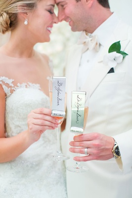 Bride and groom touch noses foreheads while holding rose champagne with metal name tags escort cards