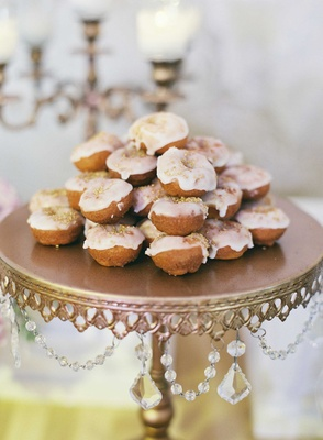 Vintage cake stand with crystal detail holding mini doughnuts with white frosting and gold sprinkles