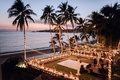 Destination wedding reception overlooking beach ocean palm trees dance floor u shaped table long