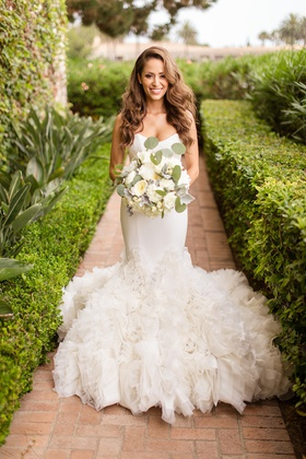 bride in ines di santo mermaid wedding dress with ruffles, glam side part hair with waves