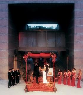 Groom kisses bride's hand under chuppah at Skirball Cultural Center