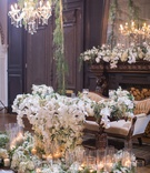 sweetheart table with vintage couch, table with cascading orchids, piles of greenery, pillar candles