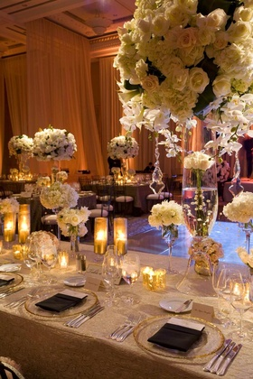 Wedding reception table with tall and small white flower arrangements and candles