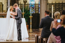 bride in custom A-line gown and chapel veil, groom in grey suit, bride and groom about to kiss
