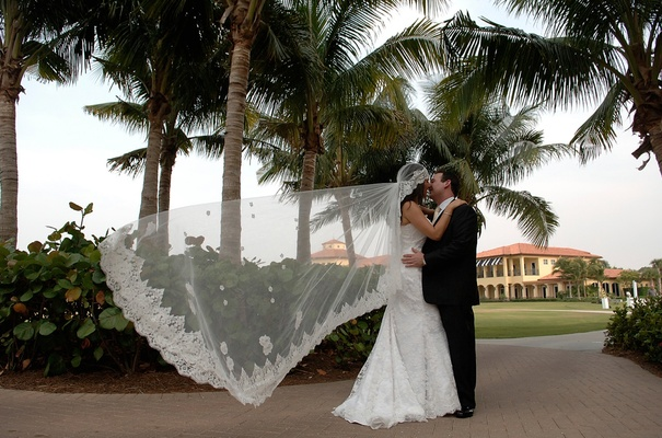 Bridal veil blowing in wind while bride kisses groom
