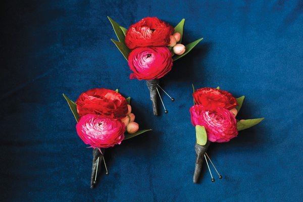 three boutonnieres made with two dark pink ranunculuses