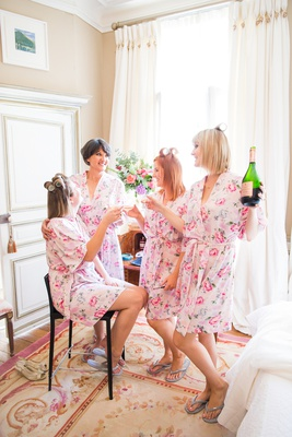bridesmaids and bride getting ready in pink white flower print robes drinking champagne hair curlers