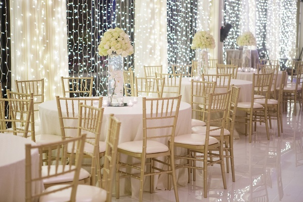 White round wedding reception table gold chairs and tall vase filled with white orchid rose flowers
