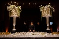 wedding reception escort card table candles flowers tall urns with lampshades orchids tulip greenery