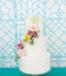 White fondant wedding cake three layer cascading fresh flowers yellow purple pink green paint