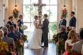 Bride in Romona Keveza wedding dress at altar with groom officiant and wedding party cross pews