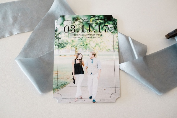Die cut save the date card on grey ribbon with engagement photo of couple walking outside large date