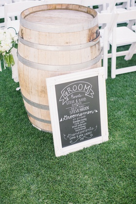 Outdoor wedding ceremony with a chalkboard program in front of a wine barrel