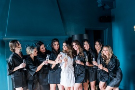 Bridesmaids in black satin robes with champagne glasses cheers bride in white robe bridesmaid photos