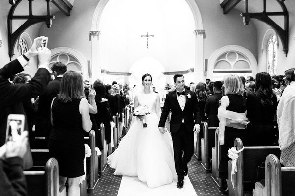 black and white photo of bride and groom recessional catholic church ceremony traditional