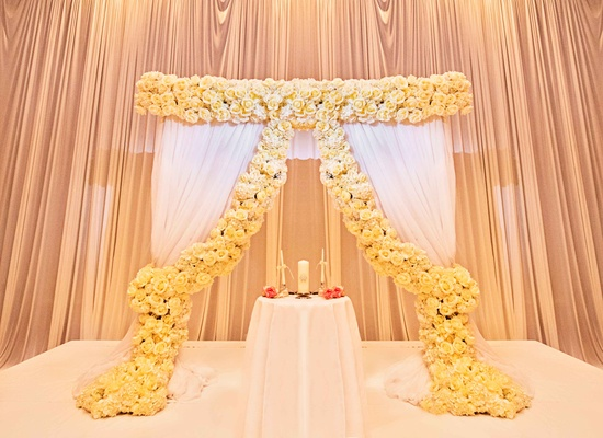 ceremony altar with white curtains and yellow roses at The Drake Hotel