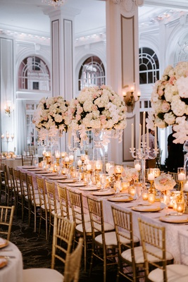 tall ceiling high ballroom white pink centerpiece flowers gold chairs chargers candles