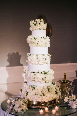 Tall white wedding cake round tiers with layers of roses ivory in between garden rose candles