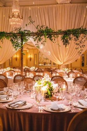wedding reception drapery chandelier greenery round table lavender linen low centerpiece green
