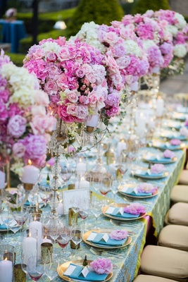 Long banquet table topped with pink floral arrangements