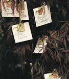 Flower motif wedding place cards hanging from tree