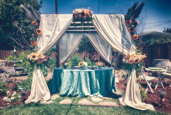 Blue table under canopy of white drapes with sunflowers