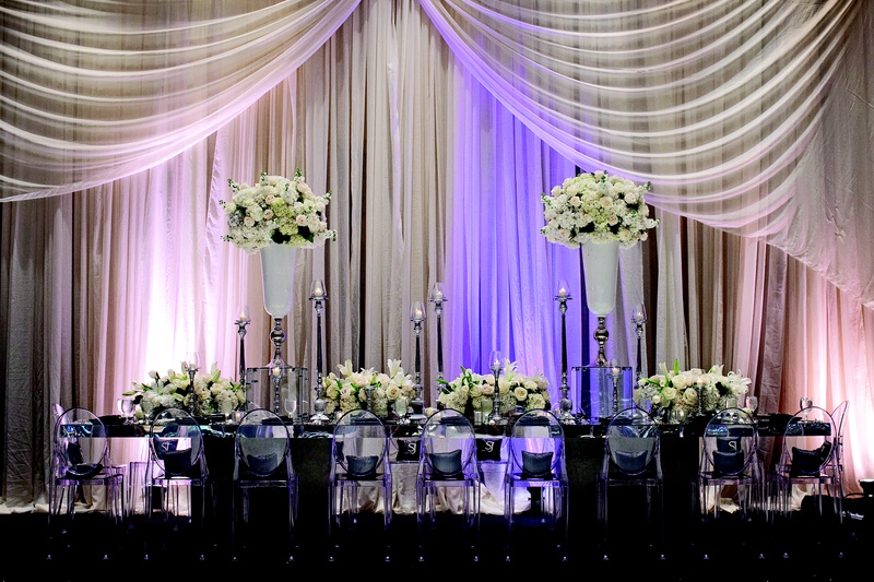 Mirror table with clear chairs in front of drapery
