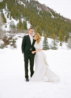 Couple in wedding attire standing in snow