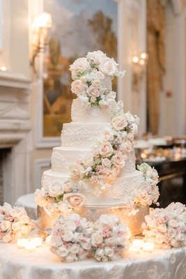 five layer regal wedding cake with fresh flowers cascading down pink and white flower decor