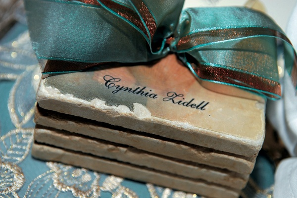 personalized gold coasters wrapped with blue ribbon