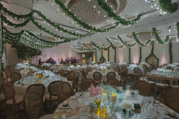 Ballroom wedding with garden theme wood chairs twinkle lights garlands low centerpieces