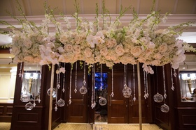 Wedding reception table with golden structure topped with light roses, white orchids, mint hydrangea