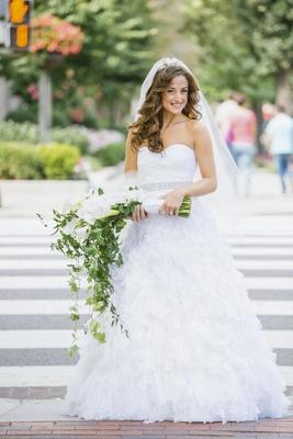 Bride in wedding dress holding long-stemmed flowers