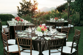 Brown reception tables with pink and green flowers