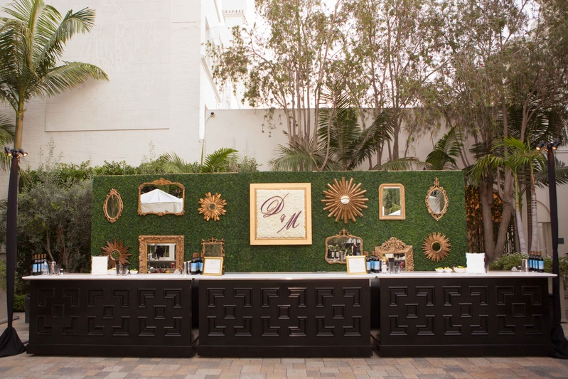 Green hedge with gallery wall and initial frame behind wedding bar