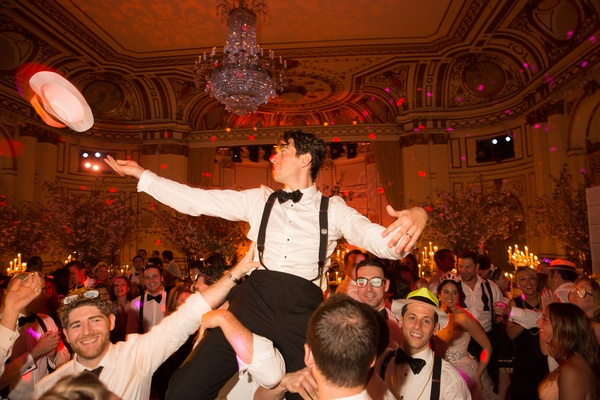 groomsmen lifting groom in chair during hora at wedding reception at the plaza