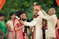 Indian bride and groom exchange garlands of red and white roses during ceremony