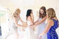 mother of the bride and bridesmaids help bride into monique lhuillier crop top dress