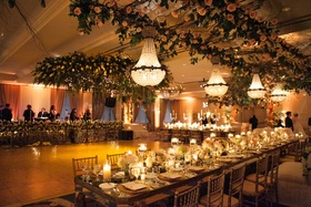 Long head table with chandelier and flowers hanging from ceiling
