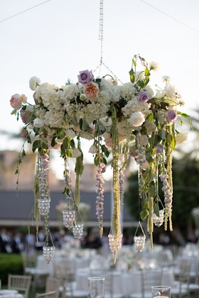 Outdoor wedding reception with chandelier made of white roses, hydrangeas, and purple roses, peonies