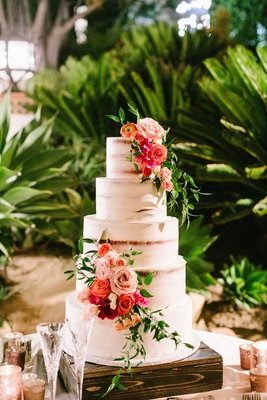 semi naked frosted wedding cake five layers fresh greenery pink orange flowers wood stand