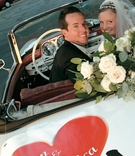 Newlyweds in decorated vintage automobile