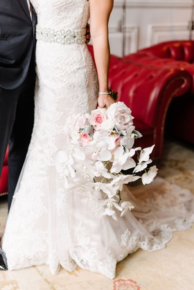 Bride in lace maggie sottero trumpet gown holding bouquet with pink peony flowers and white orchid